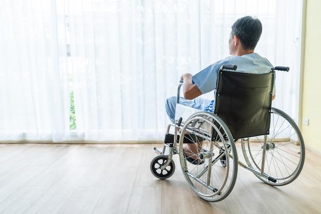 Sedia a rotelle paziente asiatica nella stanza vuota