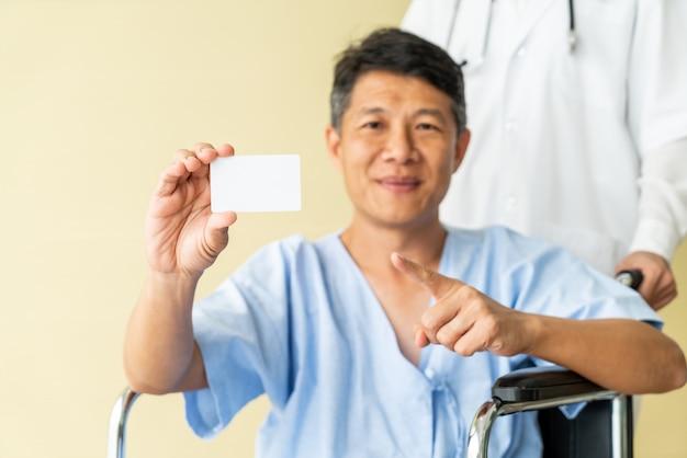 Sedia a rotelle paziente senior asiatica che sorride con la carta di credito