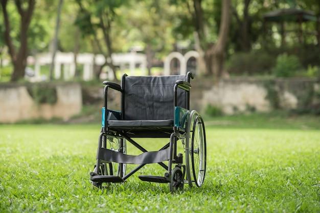 Sedia a rotelle vuota parcheggiata nel parco, concetto di assistenza sanitaria.