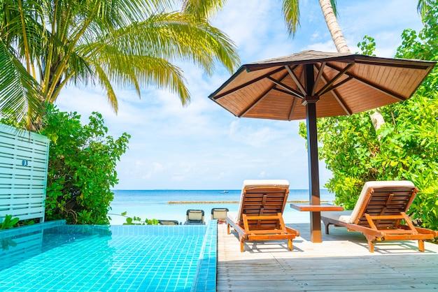 Sedia a sdraio con piscina e sfondo del mare alle maldive
