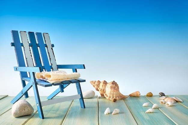 Sedia a sdraio sulla terrazza in legno con conchiglie di mare, decorazioni sul mare, copia-spazio sul blu