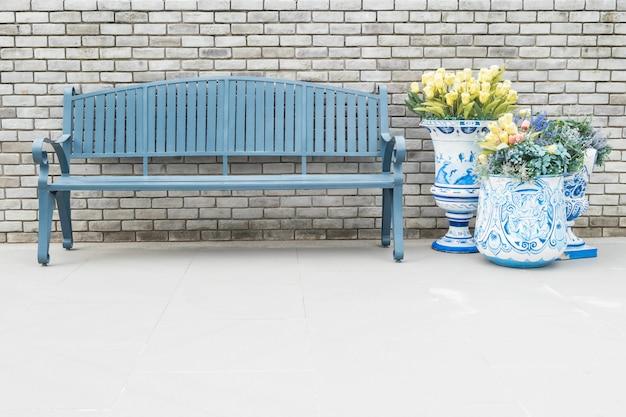 Sedia di legno del primo piano con i fiori falsi in vaso sul muro di mattoni vago