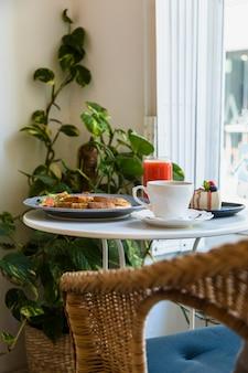 Sedia di vimini vicino al tavolo rotondo bianco con tazza di caffè; prima colazione; frullato e cheesecake