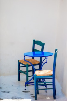 Sedia e tavola blu sulla via del villaggio tradizionale greco tipico sull'isola di mykonos, grecia, europa