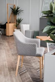Sedia grigia moderna alla moda con gambe in legno, pouf all'interno. mobili, oggetti interni, sedia di design moderno. interni eleganti e minimalisti