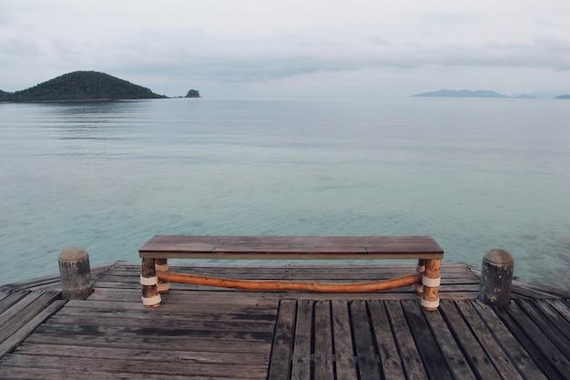 Sedia in legno con sfondo blu del mare