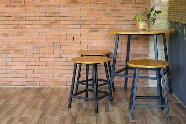 Sedia in legno e tavolo sul muro di mattoni