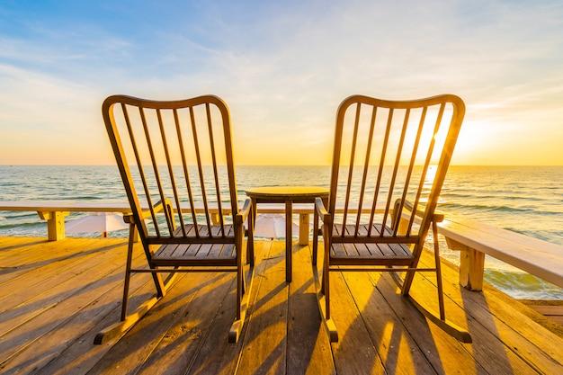 Sedia in legno vuota e tavolo al patio esterno con una bella spiaggia tropicale e mare