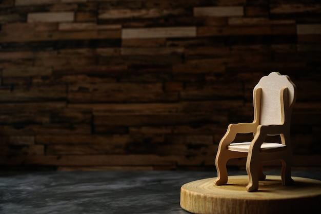 Sedia in legno vuota sul palco con tonalità chiara.