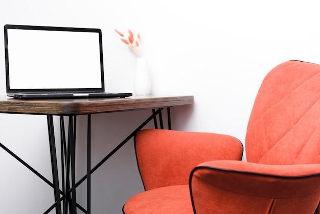 Sedia moderna del primo piano con l'ondesk del computer portatile