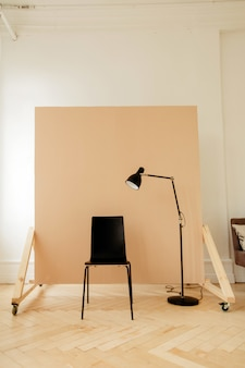 Sedia nera con lampada in camera per sessione fotografica