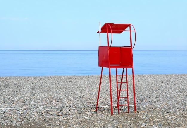 Sedia rossa del bagnino sulla spiaggia vuota