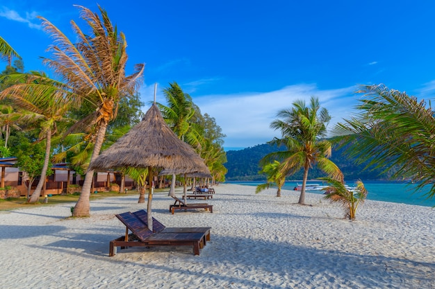 Sedie a sdraio, ombrellone e palme sulla bellissima spiaggia per vacanze e relax all'isola di koh lipe, thailandia