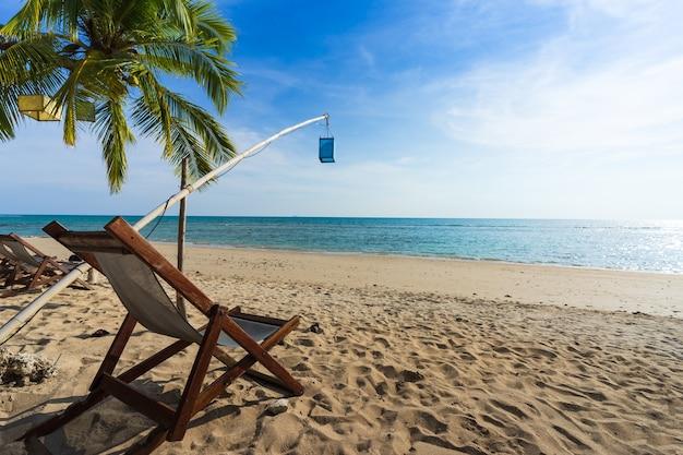 Sedie a sdraio sulla bellissima spiaggia tropicale dell'isola con luce pomeridiana.