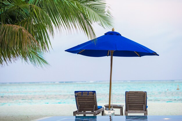 Sedie a sdraio sulla spiaggia di sabbia bianca tropicale esotica