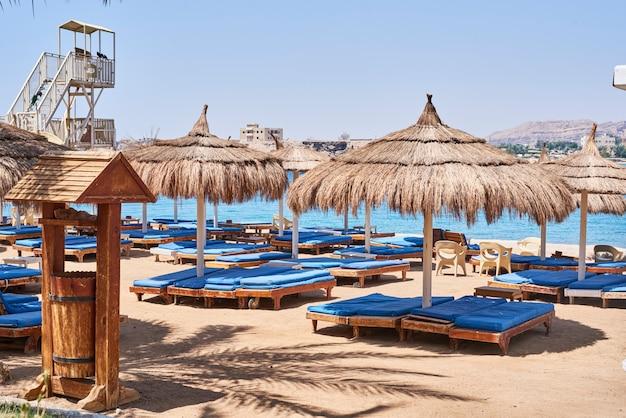 Sedie a sdraio vuote con ombrellone sulla spiaggia