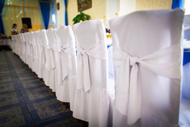 Sedie bianche con archi disposti ordinatamente in fila prima del banchetto
