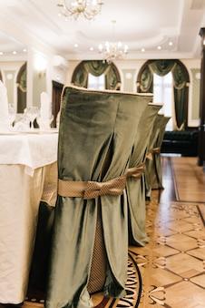 Sedie decorate. fiocco di seta legato sul retro della sedia in festa al ristorante. sedie scure della copertura del panno che stanno in una fila
