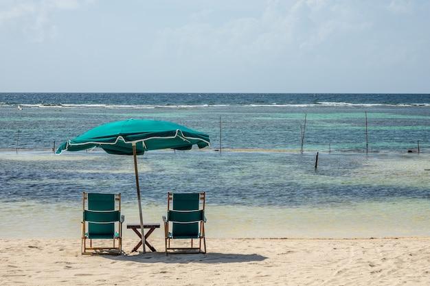 Sedie e un grande ombrellone in spiaggia in una limpida giornata di sole