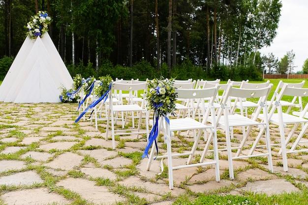 Sedie in legno bianco decorate con fiori e nastri di raso lucido, decorazioni di nozze durante la cerimonia nella pineta