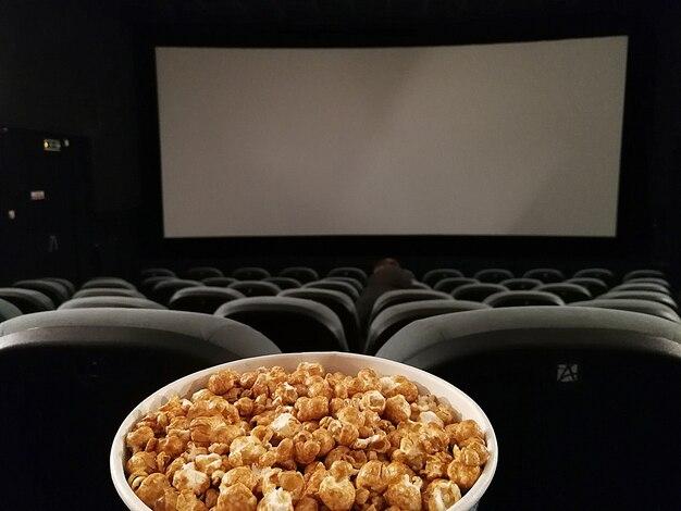 Sedile per cinema e pop corn con schermo cinematografico vuoto