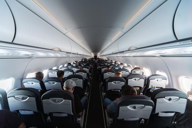Sedili cabina dell'aeroplano con passeggeri. classe economica di nuove compagnie aeree low cost più economiche senza ritardo o cancellazione del volo. viaggio di viaggio in un altro paese.
