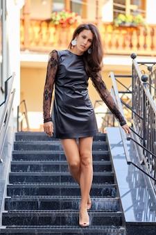 Seducente signora in abito corto di pelle che scende le scale