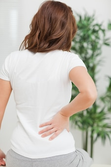 Seduta bruna mentre massaggia la schiena dolorante