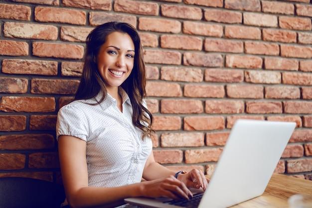Seduta castana abbastanza caucasica felice in caffè e computer portatile usando. le mani sono sulla tastiera. sullo sfondo è il muro di mattoni.