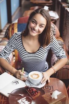 Seduta della giovane donna dell'interno in caffè urbano