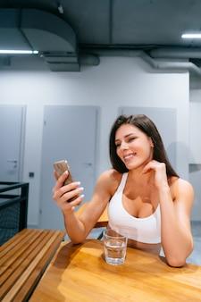 Seduta della giovane donna e smartphone usando dopo l'allenamento