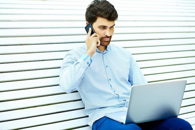 Seduta di modello del giovane uomo d'affari serio bello sulla panchina del parco facendo uso del computer portatile nel panno casuale dei pantaloni a vita bassa che parla sul telefono cellulare