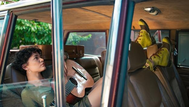 Seduta di modello in un'automobile con una chitarra che posa per un servizio fotografico