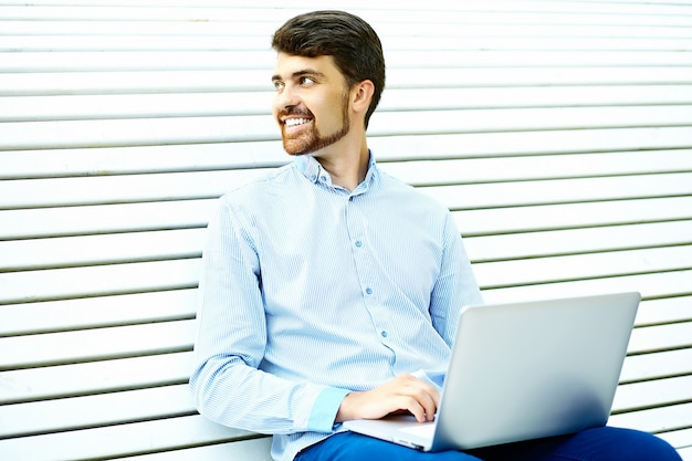 Seduta di modello sorridente giovane bello dell'uomo d'affari sul banco di parco facendo uso del computer portatile nel panno casuale dei pantaloni a vita bassa