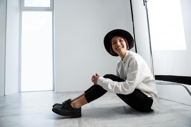Seduta di risata della giovane bella ragazza sul pavimento sopra la parete bianca.