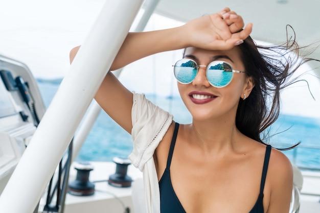 Seduta e guida castana attraenti e splendide di una barca a motore moderna. ragazza adorabile che si rilassa e che posa per la macchina fotografica. modella indossa bikini nero. vacanze estive di lusso