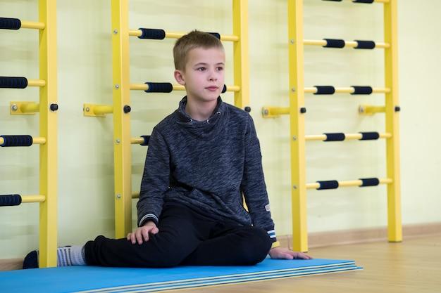 Seduta e relaxiong del ragazzo del bambino piccolo sul pavimento dentro la sala sportiva in una scuola dopo l'allenamento.