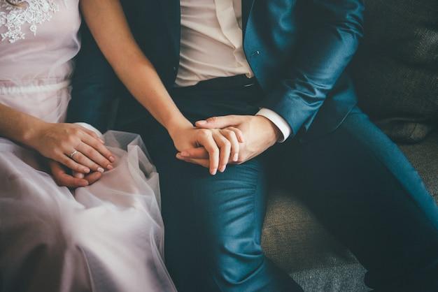 Seduta elegante della sposa e dello sposo. tenendosi per mano, da vicino