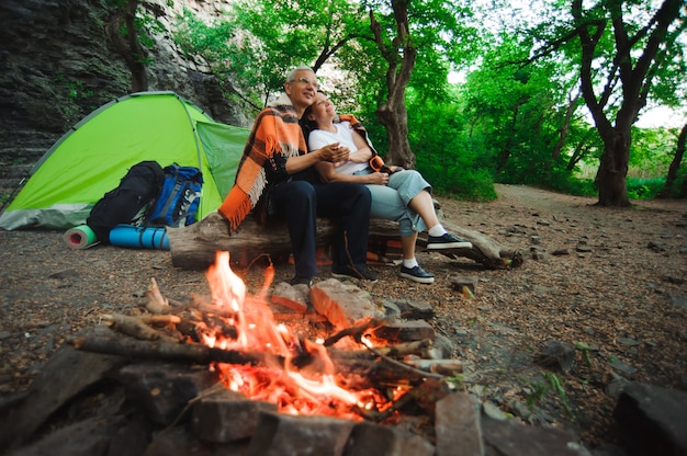 Seduta romantica delle coppie di campeggio della tenda dalla campagna di notte del falò.