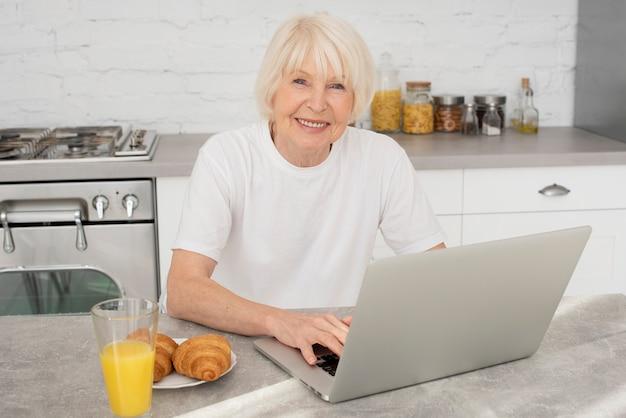 Seduta senior felice nella cucina con un computer portatile