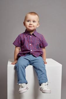 Seduta sorridente del giovane ragazzo del bambino su un cubo bianco