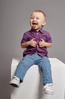 Seduta sorridente del giovane ragazzo del bambino sul cubo bianco