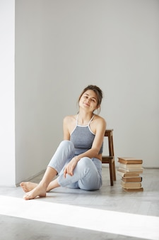Seduta sorridente della bella donna tenera sul pavimento con i libri sopra la parete bianca.