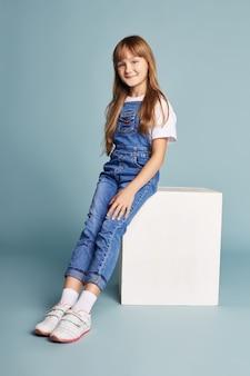 Seduta sorridente della bella ragazza su un cubo