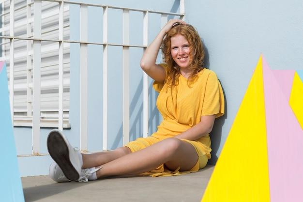 Seduta sorridente della donna di smiley della foto a figura intera