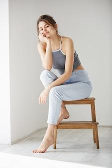 Seduta sorridente della giovane bella donna tenera sulla sedia sopra la parete bianca.