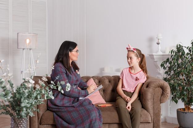 Seduta sorridente della ragazza su un sofà accanto ad un terapista femminile di seduta del medico