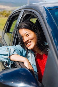 Seduta sorridente femminile asiatica in automobile