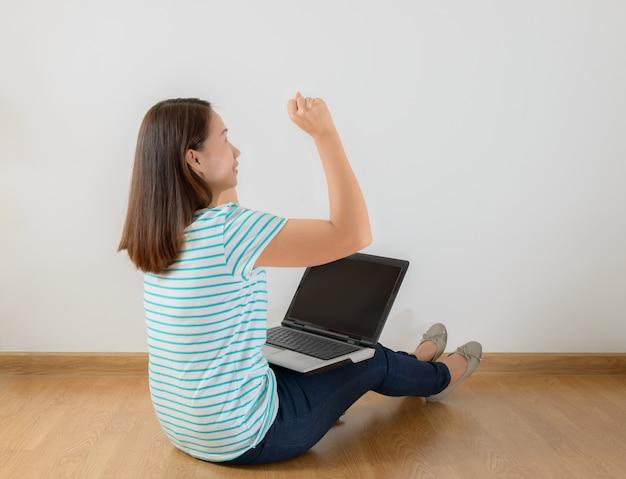 Seduto per terra con un portatile alzando le braccia con uno sguardo di successo