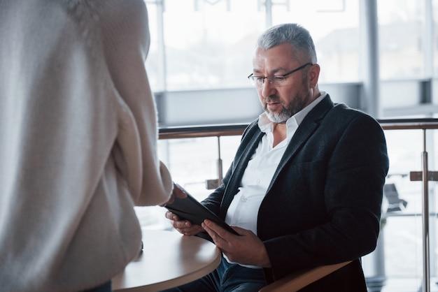 Seduto vicino al tavolo e leggendo i documenti forniti dal dipendente di fronte a lui